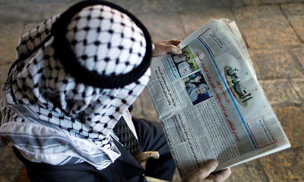 Ein Palästinenser liest in einer Zeitung über die US-Wahl.