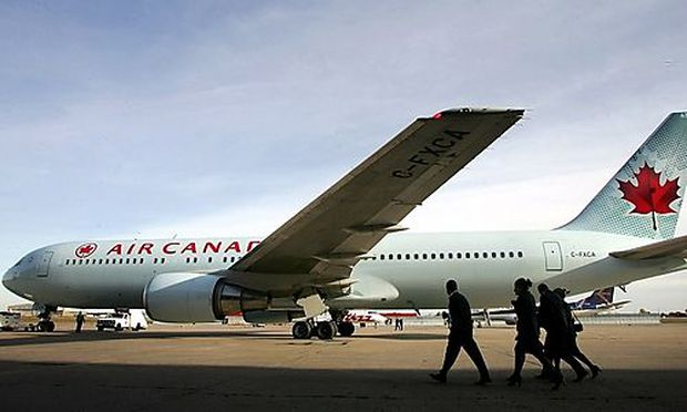 File photo of an Air Canada flight crew walking past the newly unveiled aircraft colors at the Montre