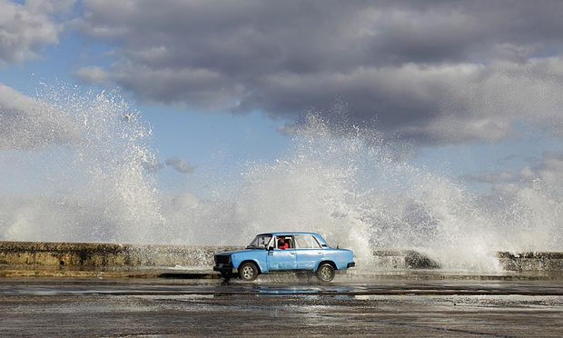 A Russian-made Lada car drives past as waves break on Havana´s seafront boulevard ´El Malecon´