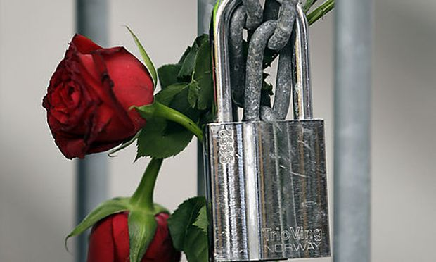 Roses are fixed on a fence to commemorate the victims in front of the Oslo court where Norwegian Ande