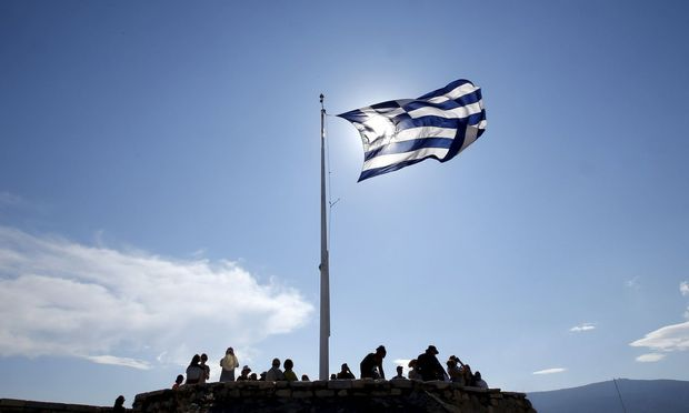 A Greek flag flutters as tourists visit the Acropolis hill archaeological site in Athens