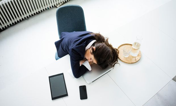 Overworked businesswoman sleeping on laptop in office, top view