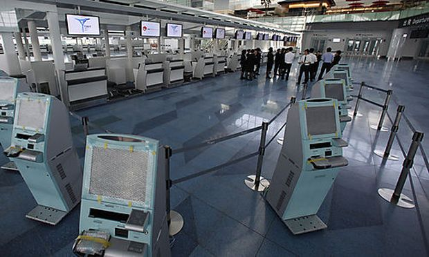 In this photo taken on Aug. 23, 2010, airport staff gather at a ticketing counter, getting ready for