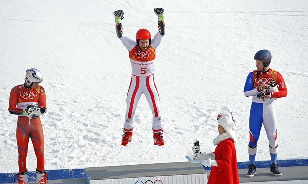 """Auch beim """"Podest-Jump"""" der Konkurrenz sichtlich überlegen und Bewunderung abringend: Marcel Hirscher zeigt es vor, Henrik Kristoffersen (li.) und Alexis Pinturault (re.) staunen.  / Bild: (c) REUTERS (MIKE SEGAR)"""