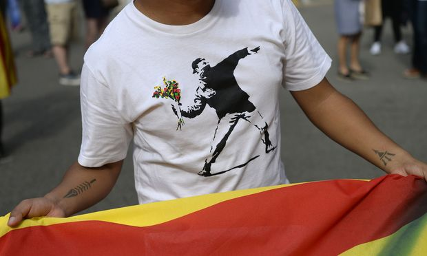 Die Wut auf Madrid wächst: Ein katalanischer Demonstrant trägt auf seinem T-Shirt ein Symbol für den friedlichen Protest gegen die Polizeigewalt.