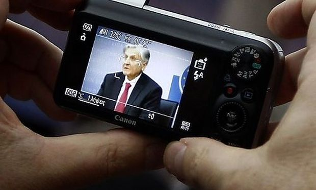 A reporter takes a photograph of Trichet, President of the European Central Bank (ECB) as he answers