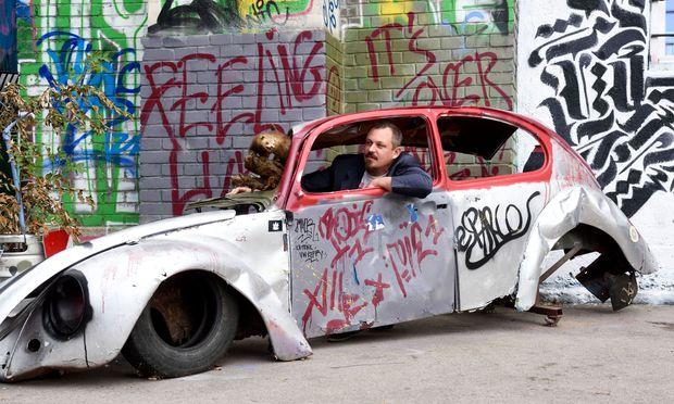 Stefan Stürzer, Direktor des Werk, mit seinem ausgestopften Marder. Das Tier, das er von einem Freund geschenkt bekam, ist eine Art Maskottchen, das immer auf seinem Schreibtisch steht. Wenn er nicht gerade mit ihm im Autowrack vor den Stadtbahnbögen des Werk am Donaukanal posiert.