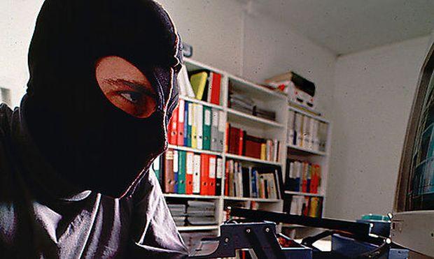 Mann mit Maske sitzt vor einem Computer-Computerkrimineller