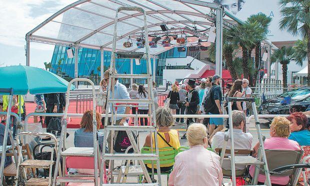 Schon bevor das Filmfestival startet, haben die Paparazzi und Schaulustigen am Absperrgatter vor dem Palais des Festivals ihre mit Namensschildern versehenen Leitern und Trittbretter festgekettet