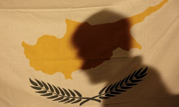 A protester casts his shadow onto a Cypriot flag during an anti-bailout rally outside the presidential palace in Nicosia