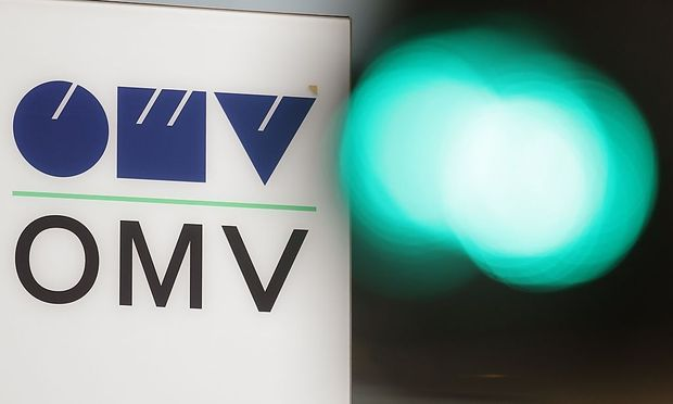The logo of Austrian oil and gas company OMV is pictured behind traffic lights at its headquarters in Vienna