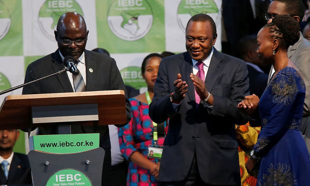 Incumbent President Uhuru Kenyatta applauds after he was announced winner of the presidential election at the IEBC National Tallying centre at the Bomas of Kenya