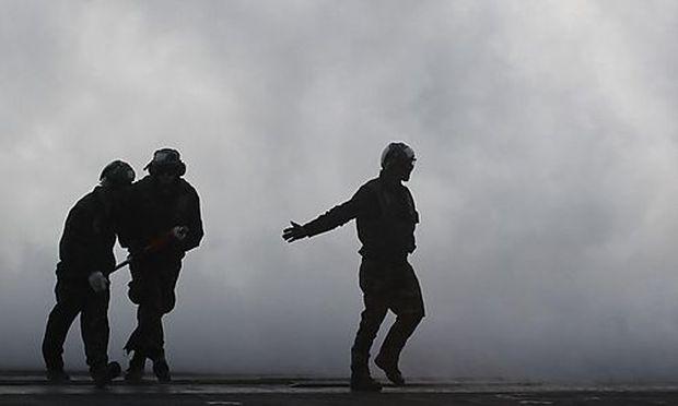 A flight deck crew member gestures after a U.S. Navy F/A-18F Super Hornet took off from the U.S. Navy