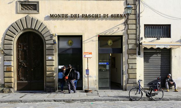 People use a cash machine of Monte Dei Paschi bank in downtown in Florence