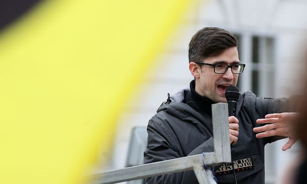 Leader of Austria's Identitarian Movement Martin Sellner speaks during a protest against a police raid at his house, outside the Justice Ministry in Vienna