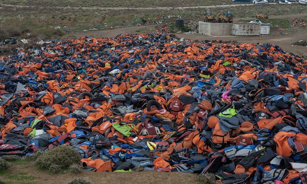 February 27 2016 Lesbos Greece A pile of lifejackets left behind by refugees and migrants who