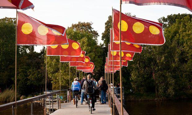 Christiania, die in den 1970ern gegründete Enklave: grünes Stück mitten in Kopenhagen, aber von seiner Einstellung heute nicht grüner als der Rest von Dänemark. Fahnen markieren die Quasiausnahmezone.