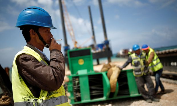 Chinese construction workers work during a media tour of the construction of a new port in the southern city of Ashdod