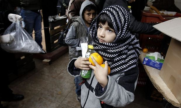 A child makes his way after receiving food from the Orthodox Church of Greece in Athens