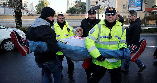 Ein Demonstrant wird von der Polizei unsanft abgeführt.