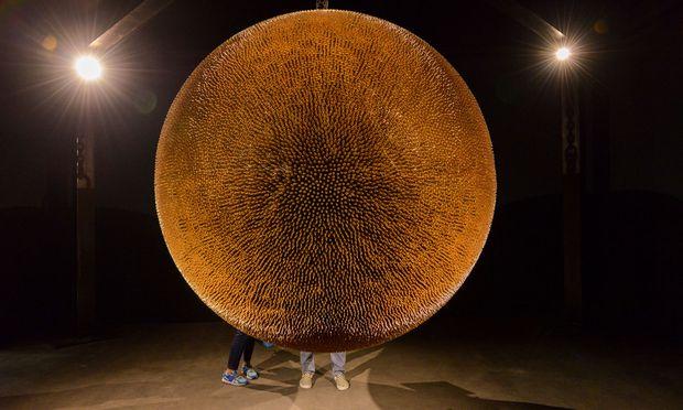 Dieser schimmernde Ball von Robert Longo besteht aus 40.000 Patronenhülsen und ist auf der Art Unlimited zu sehen.  / Bild: (c) Art Basel