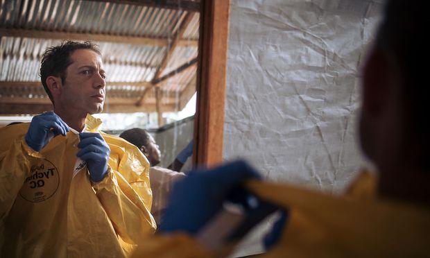 Die gefährlichste Situation des Tages: Tropenarzt Christian Kleine beim Anziehen der Ebola-Schutzkleidung.