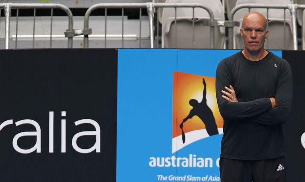 Djokovic of Serbia serves as his fitness coach Phil-Gritsch watches during a practice session at the Australian Open tennis tournament in Melbourne