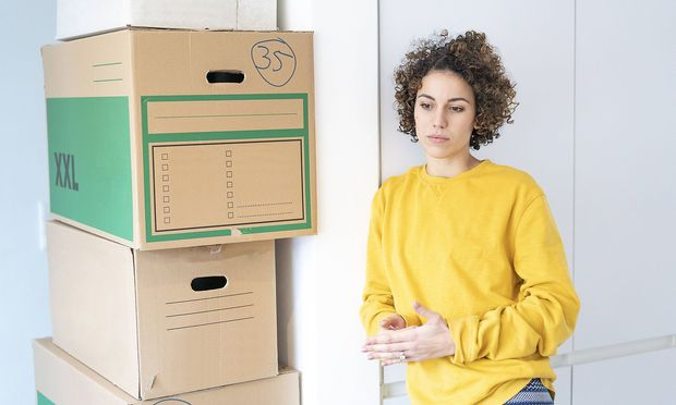 Serious woman at home with cardboard boxes model released Symbolfoto property released PUBLICATIONxI