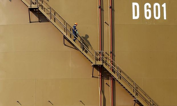File photo of a worker walking down the stairs of an oil tank at Turkey's Mediterranean port of Ceyhan