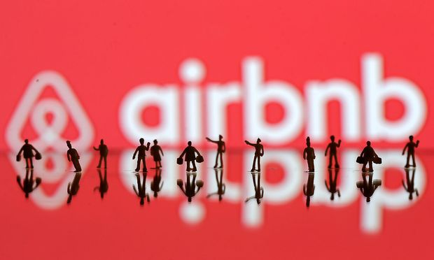 A 3D printed people models is seen in front of a displayed Airbnb logo in this illustration taken
