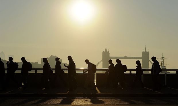 Workers cross London Bridge, with Tower Bridge seen behind, during the morning rush hour in London