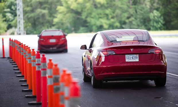 IIHS media relations associate Young demonstrates front crash prevention test on Tesla Model 3 at IIHS-HLDI Vehicle Research Center in Ruckersville, Virginia