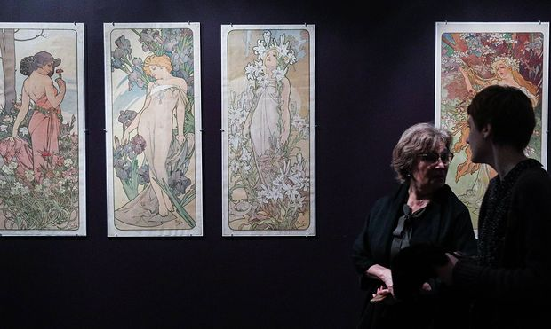 MOSCOW RUSSIA FEBRUARY 20 2019 Visitors walk past posters by Alphonse Mucha on display at an e