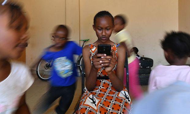 Das Mobiltelefon hat Afrika völlige neue Entwicklungsmöglichkeiten eröffnet. / Bild: APA/AFP/TONY KARUMBA