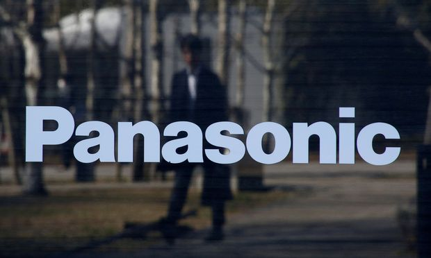FILE PHOTO: A man is reflected on Panasonic Corp's logo at Panasonic Center in Tokyo