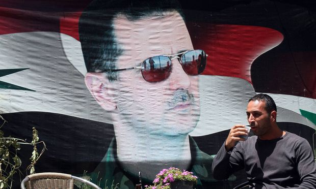 A Syrian man takes a drink beside a poster of Syria s President Bashar al Assad in Damascus capita