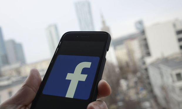The Facebook icon is seen on an iphone in this photo illustration Hand holding an iPhone with city