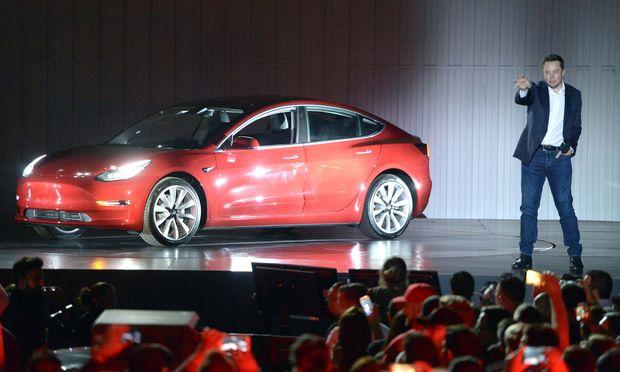 Elon Musk mit dem Hoffnungsauto Teslas, dem Model 3 (im Juli 2017 bei einer Präsentation).