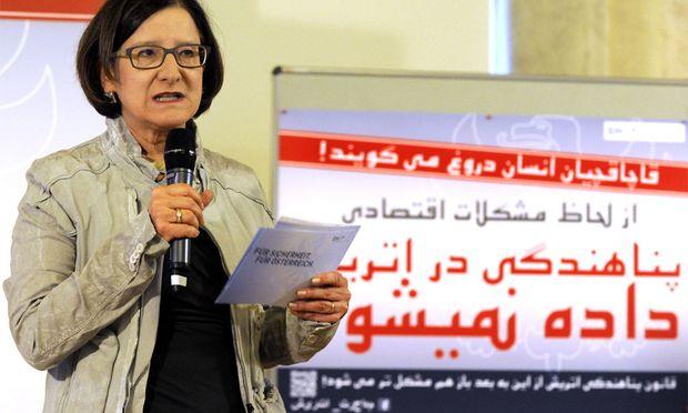 Mikl-Leitner vor einem Plakat auf Dari, das Teil der Infokampagne des Innenministeriums ist.