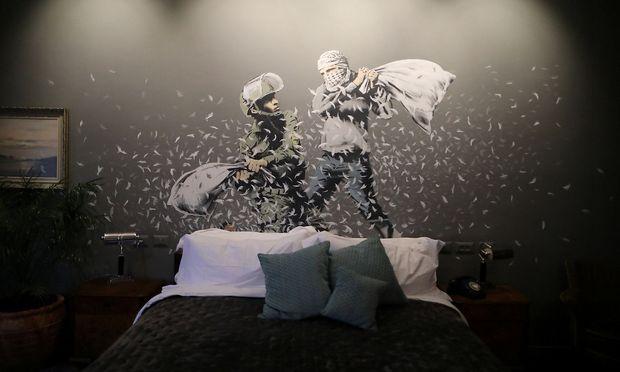 """Graffiti über einem Bett im """"Walled Off Hotel""""."""