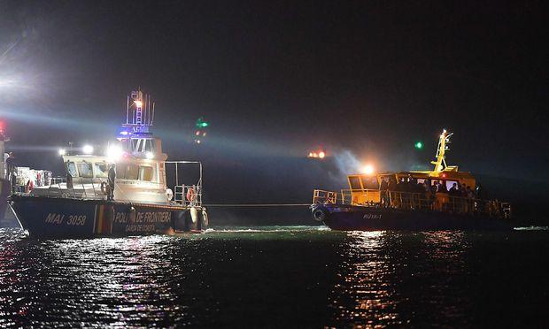 Rumänisches Wachboot mit dem Migrantenboot im Schlepptau