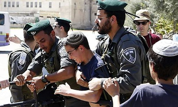 Israeli border policemen hold back a Jewish youth to prevent him from reaching a building occupied by