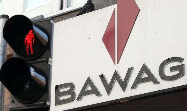 A pigeon sits atop the logo of Austrian lender BAWAG PSK next to traffic lights at a branch office in Vienna