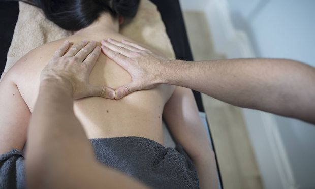 Physio massaging woman s back model released Symbolfoto property released PUBLICATIONxINxGERxSUIxAUT