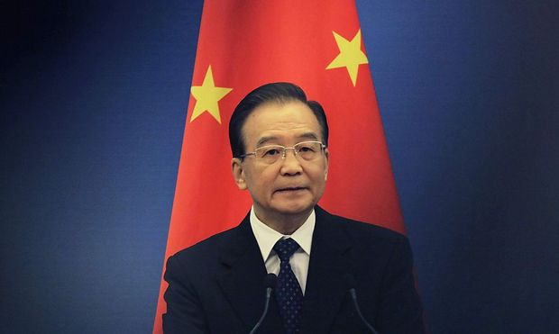 File photo of China's Premier Wen Jiabao standing in front of a Chinese national flag at the Great Hall of the People in Beijing