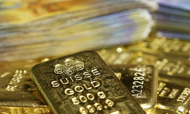 Gold bars and Swiss Franc banknotes are seen in this illustration picture in Vienna
