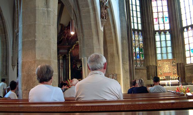 Wenige Besucher in einer Kirche bei der Sonntagsmesse