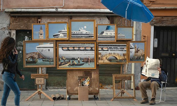 Social media picture of a street stall with oil paintings creating an image of a yacht in the Venice canal with a sign reading ´Venice in oil´, set up by a person purporting to be British artist Banksy, in Venice