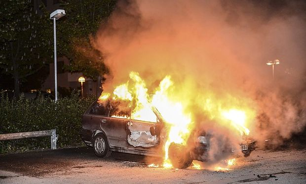 A car set on fire burns following riots in the Stockholm suburb of Kista