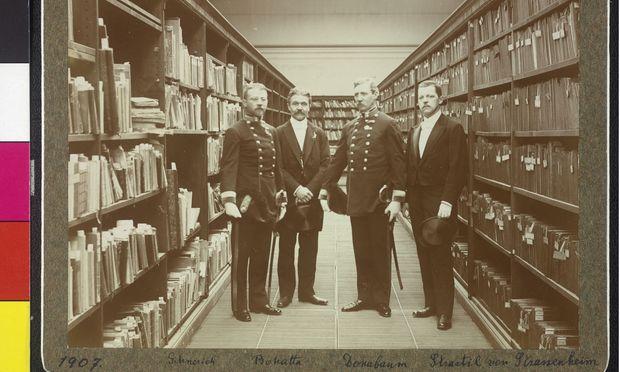 Bedauerlicherweise noch ohne Frauenanteil, dafür aber mit Uniform: Vier Beamte aus der Endzeit der österreichisch-ungarischen Monarchie im Magazin der Universitätsbibliothek Wien (1907).